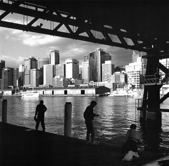 Boys fishing under Pyrmont Bridge with afternoon light on the city – 1992